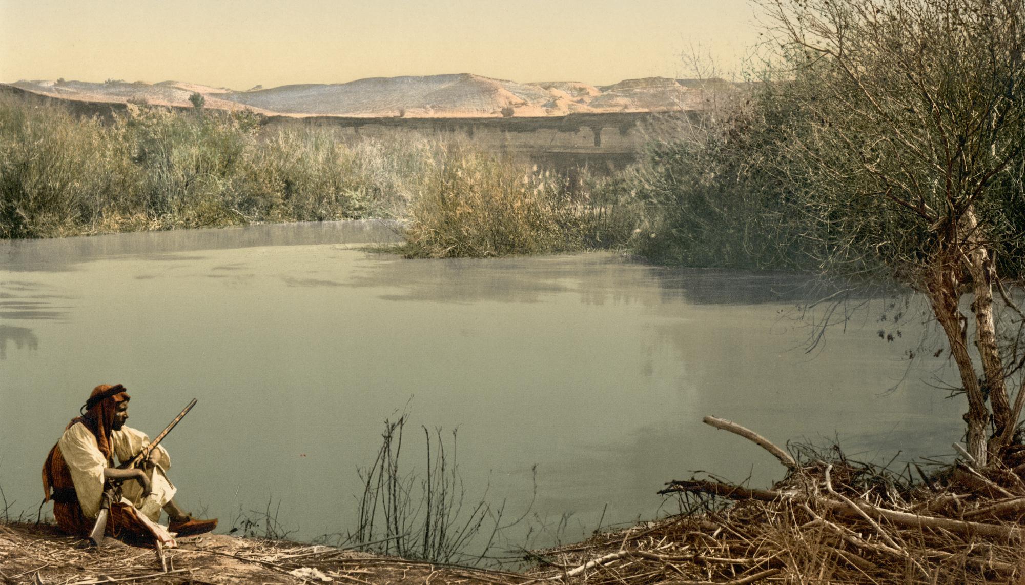 رجل جالس على نهر الأردن.