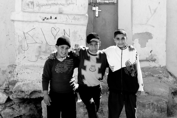 Three kids pose for the camera in front of their house in Jabal Amman